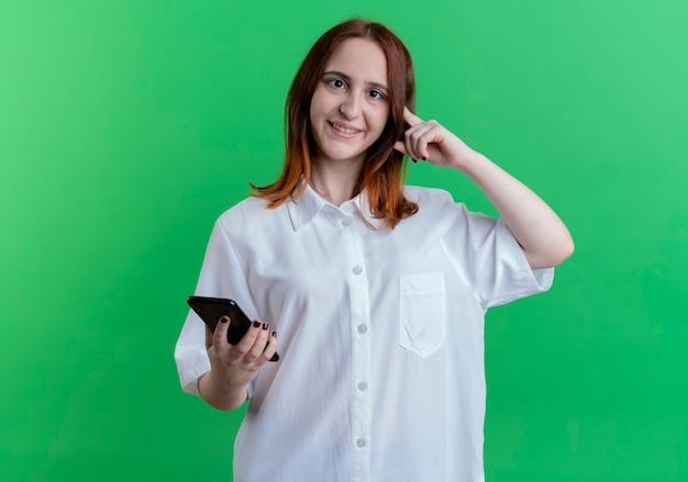 Sonriente joven pelirroja sosteniendo el teléfono y poniendo el dedo en la cabeza aislada en verde