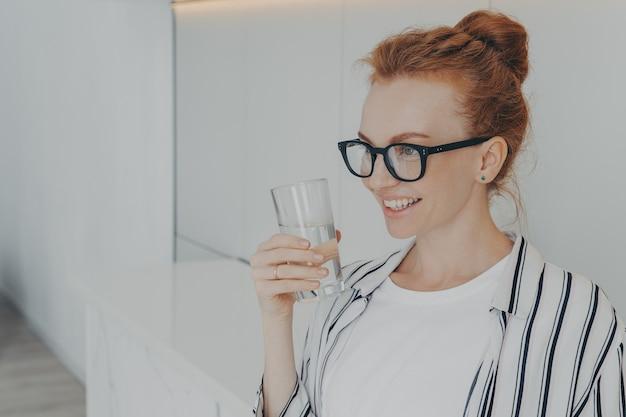 Sonriente joven pelirroja sostiene un vaso de agua bebe aqua para refrescarse el cuerpo