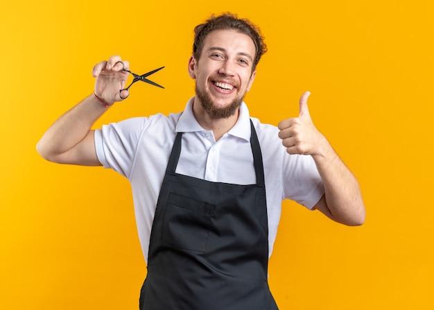 Sonriente joven peluquero vistiendo uniforme sosteniendo unas tijeras mostrando el pulgar hacia arriba aislado sobre fondo amarillo