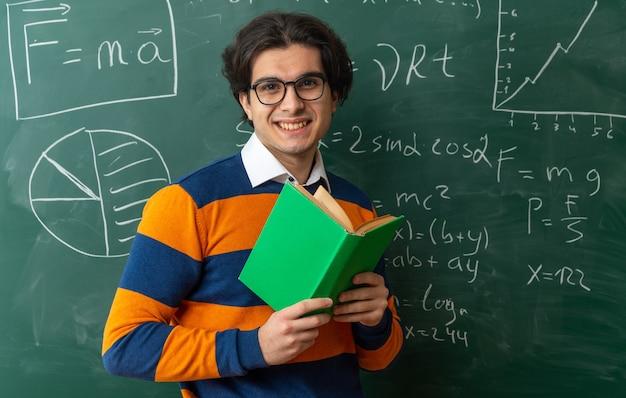 Sonriente joven profesor de geometría con gafas de pie delante de la pizarra en el aula sosteniendo el libro abierto mirando al frente