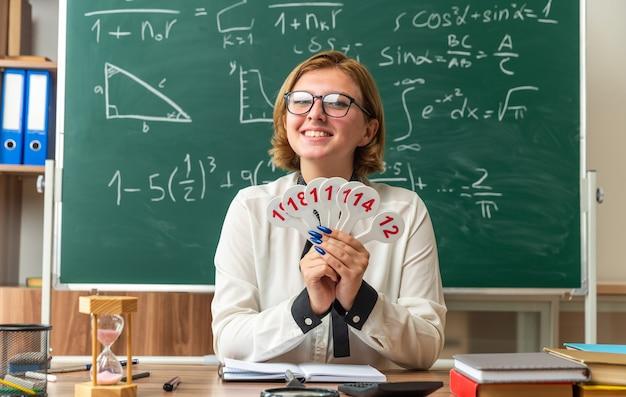Sonriente joven profesora con gafas se sienta a la mesa con útiles escolares sosteniendo el número de ventiladores en el aula