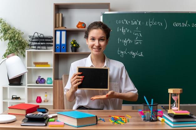 Sonriente joven profesora de matemáticas sentada en un escritorio con útiles escolares sosteniendo una mini pizarra apuntando con la mano mirando al frente en el aula