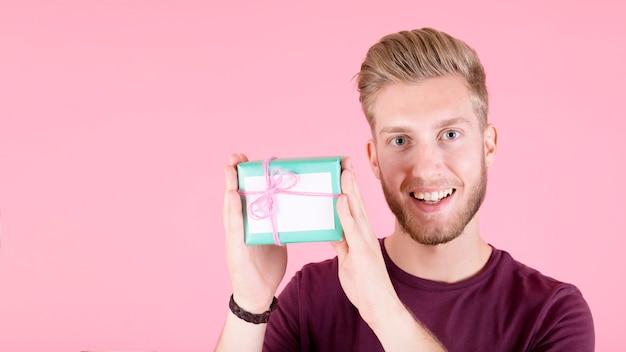 Sonriente joven que muestra la caja de regalo sobre fondo rosa