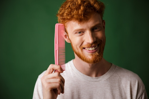 Sonriente joven readhead beardy hombre mostrando peine rosa
