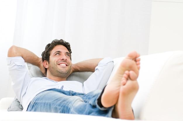 Sonriente joven relajante y soñando en el sofá en casa