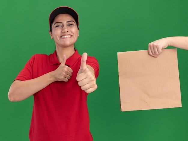 Sonriente joven repartidora vestida con uniforme y gorra mostrando el pulgar hacia arriba a alguien que le da dinero aislado en la pared verde