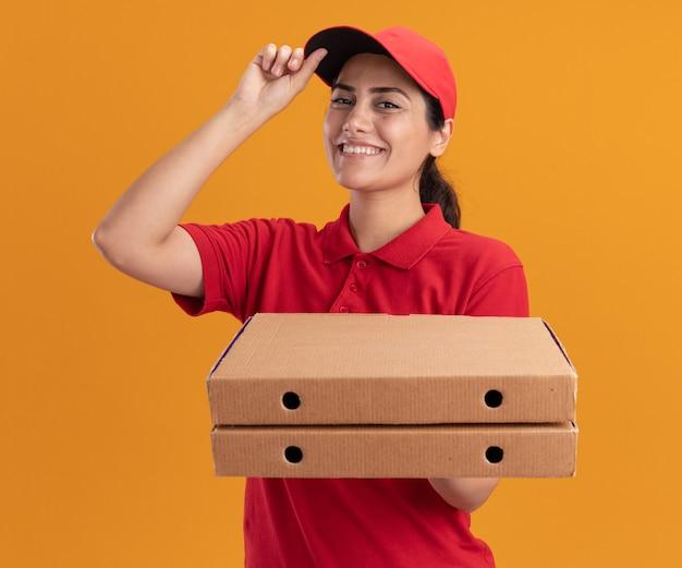 Sonriente joven repartidora vestida con uniforme y gorra sosteniendo cajas de pizza y gorra aislada en la pared naranja