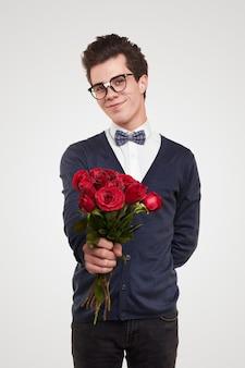 Sonriente joven romántico en ropa nerd y gafas dando ramo de rosas rojas hacia mientras saluda el día de san valentín