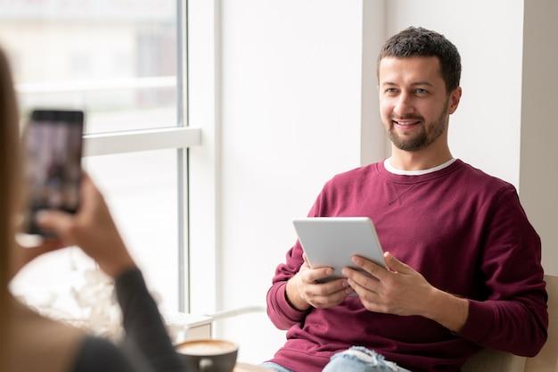 Sonriente joven en ropa casual mirando a la novia tomando su foto en el teléfono inteligente mientras ambos se relajan en la cafetería