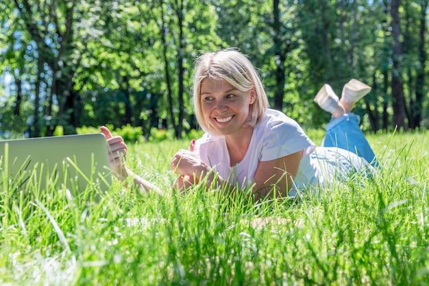 Sonriente joven rubia se encuentra en el césped en un parque con un ordenador portátil en un día soleado de verano.