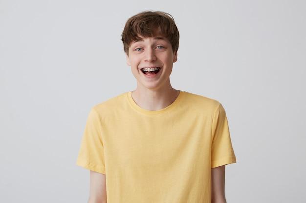 Sonriente joven rubio emocionado con corte de pelo corto y tirantes de metal en los dientes viste camiseta amarilla y se ve feliz