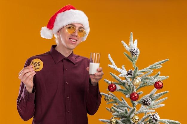 Sonriente joven rubio con gorro de papá noel y gafas de pie cerca del árbol de navidad decorado con vaso de leche y galletas mirando a cámara aislada sobre fondo naranja