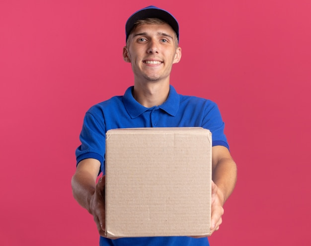 Sonriente joven rubio repartidor sostiene cardbox