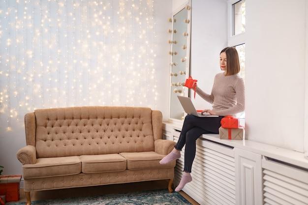 Sonriente joven saludando a amigos con navidad en video chat en portátil con cajas de regalo