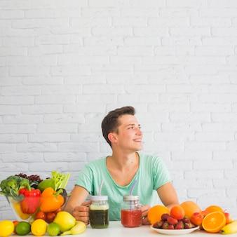 Sonriente joven sentado detrás de la mesa con frutas y verduras frescas maduras