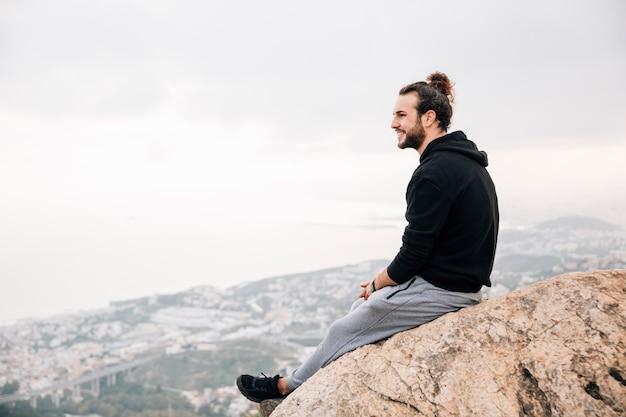 Sonriente joven sentado en el pico de la montaña mirando el paisaje urbano