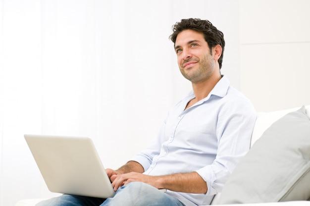 Sonriente joven soñando mirando hacia arriba mientras trabaja en la computadora portátil