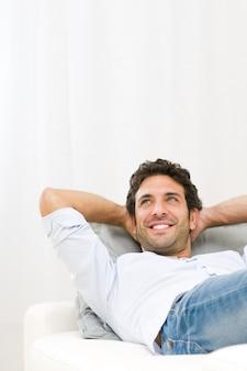 Sonriente joven soñando con su futuro y relajándose en el sofá en casa
