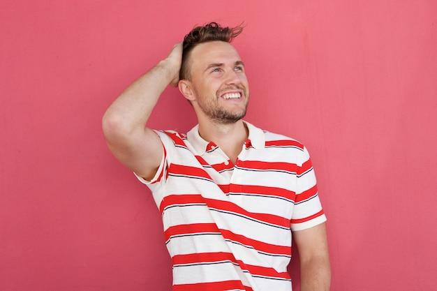 Sonriente joven sonriendo contra la pared roja con la mano en el pelo