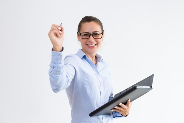 Sonriente joven sosteniendo archivo y escribiendo en el aire