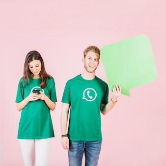 Sonriente joven sosteniendo el bocadillo de diálogo al lado de la mujer que usa el teléfono inteligente