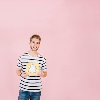 Sonriente joven sosteniendo el icono de snapchat en fondo rosa