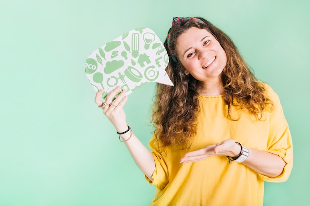 Sonriente joven sosteniendo la burbuja del discurso contra el fondo en colores pastel