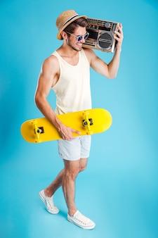 Sonriente joven sosteniendo radio y patineta amarilla