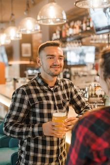 Sonriente joven sosteniendo un vaso de cerveza con su amiga