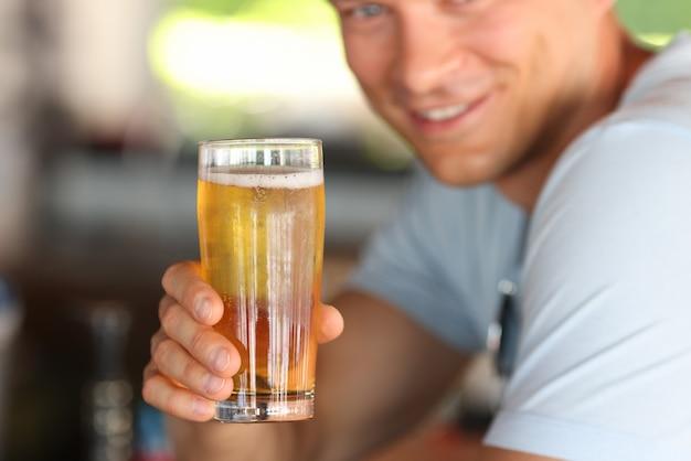 Sonriente joven sosteniendo un vaso de cerveza