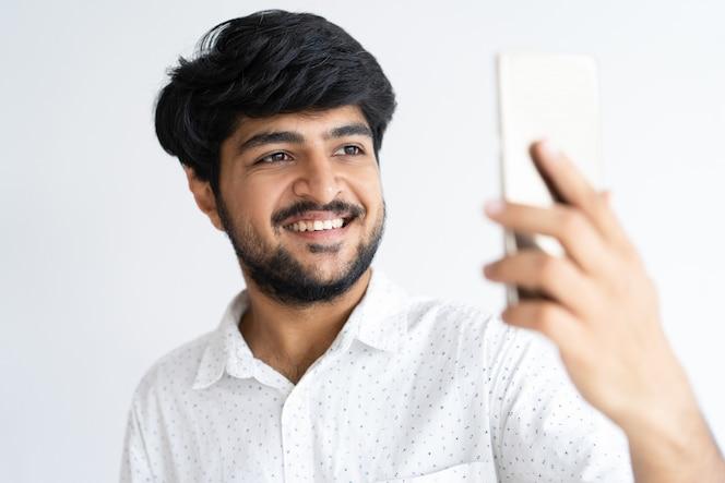 Sonriente joven tomando foto selfie en smartphone. chico indio con dispositivo digital