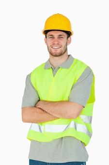 Sonriente joven trabajador de la construcción con los brazos cruzados
