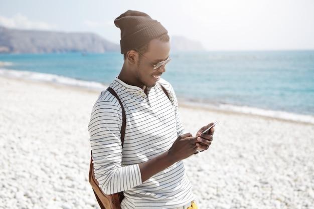 Sonriente joven turista europeo masculino negro con sombrero y sombras usando 3g de internet en el teléfono móvil en la playa, compartiendo fotos a través de las redes sociales, disfrutando de días felices durante sus vacaciones de verano en la playa