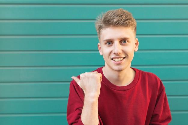 Sonriente joven en turquesa muestra un dedo a un lado en copyspace
