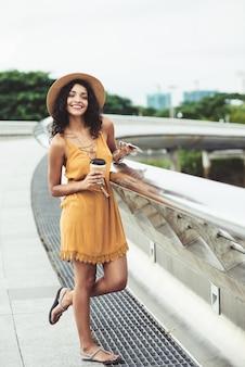 Sonriente joven vestida casualmente posando en la orilla del río