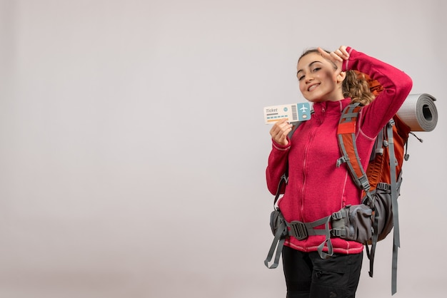 Sonriente joven viajero con mochila grande sosteniendo boleto de viaje en gris