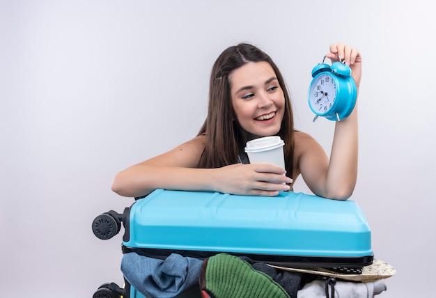 Sonriente joven viajero mujer sosteniendo despertador y viajando taza de café de plástico con maleta en pared blanca aislada
