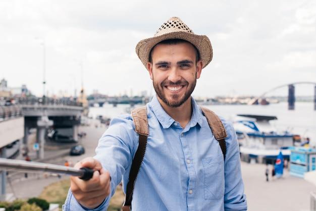 Sonriente joven viajero con sombrero y tomando selfie al aire libre
