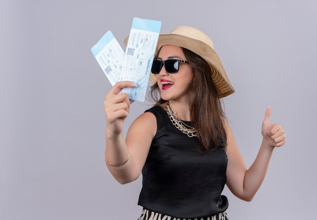 Sonriente joven viajero vistiendo camiseta negra con sombrero en gkasses holdings tickets su pulgar hacia arriba sobre fondo blanco.