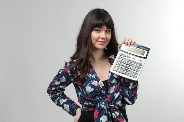 Sonriente jovencita en camiseta diseñada de buen humor con calculadora con cabello largo en blanco