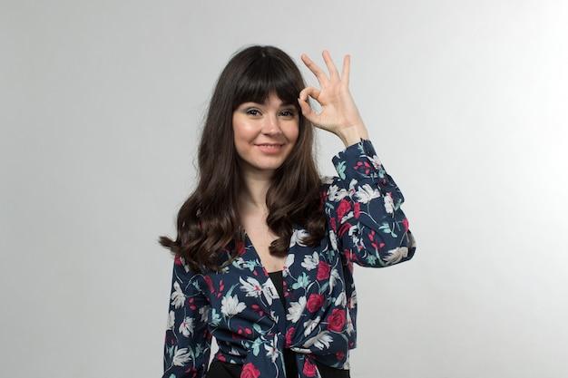 Sonriente jovencita en camiseta diseñada de buen humor con el pelo largo en blanco