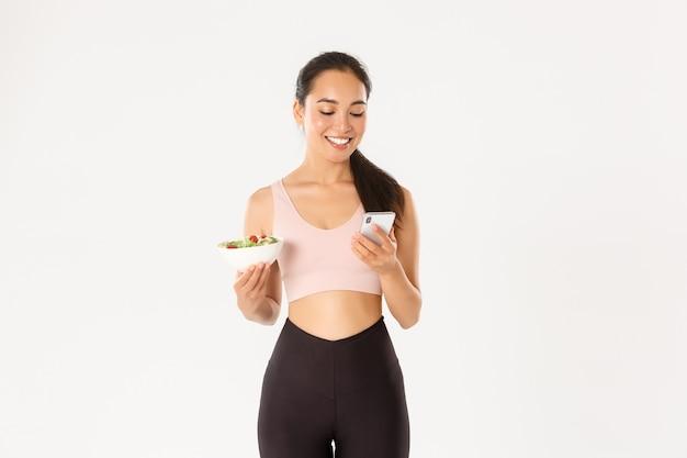 Sonriente linda chica asiática que usa la aplicación de dieta, la aplicación de seguimiento de calorías en el teléfono móvil, comuníquese con el entrenador para informar sobre el consumo de alimentos, sostenga la ensalada.