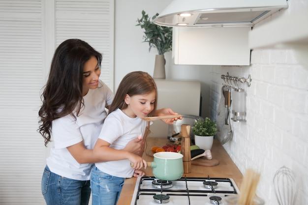 Sonriente madre e hija cocinando en la cocina de estilo escandinavo en blanco