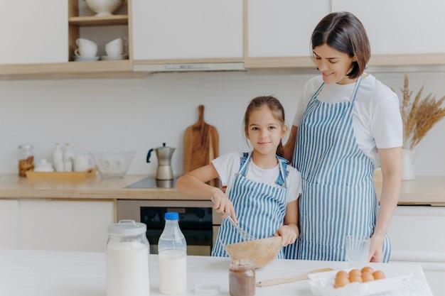 Sonriente madre e hija preparan galletas sabrosas