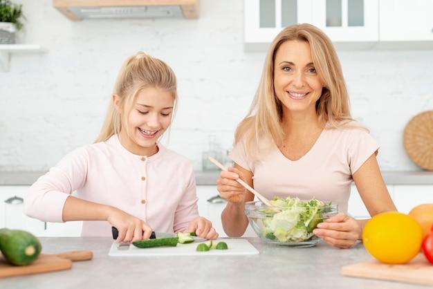 Sonriente madre e hija preparando ensalada