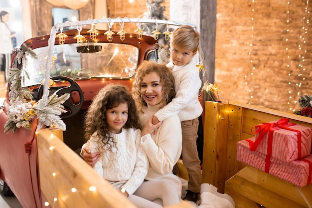 Sonriente madre feliz con su hijo e hija en el remolque de recogida de coche rojo cerca de árboles de navidad y luces