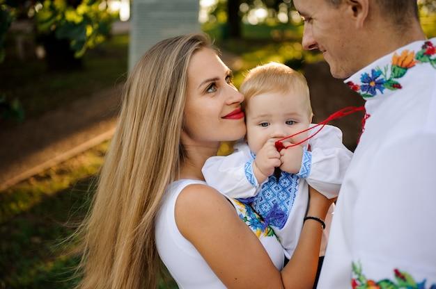 Sonriente madre y padre sosteniendo en las manos un bebé vestido con la camisa bordada