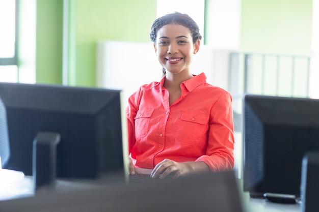 Sonriente maestra usando la computadora