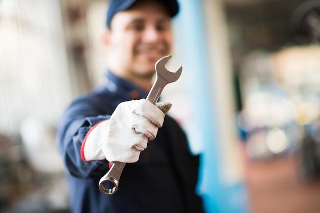Sonriente mecánico sosteniendo una llave inglesa en su tienda