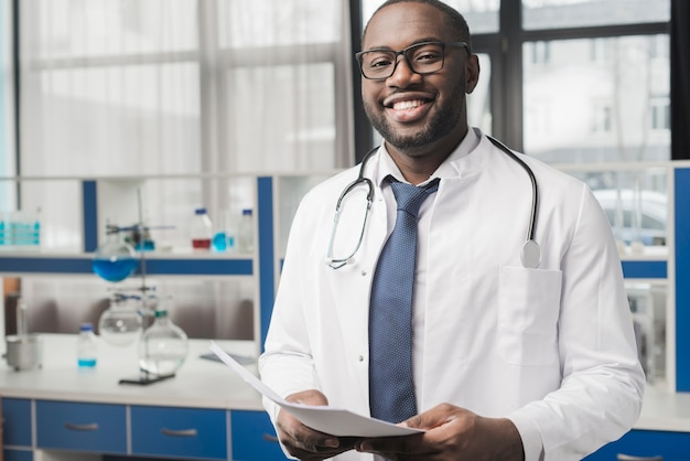Sonriente médico negro con papeles